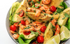 A close-up of shrimp, lime wedges, avocado wedges, and cherry tomatoes seasoned with herbs in a white bowl.