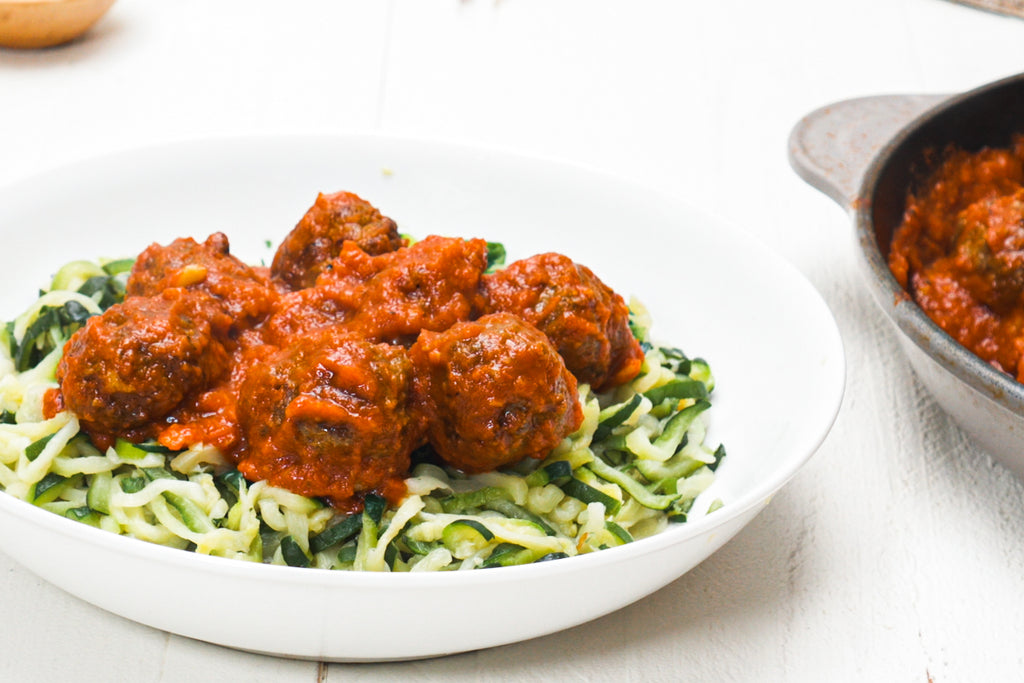 Zoodles with Primal Kitchen Roasted Garlic Marinara and grass-fed meatballs on a white plate