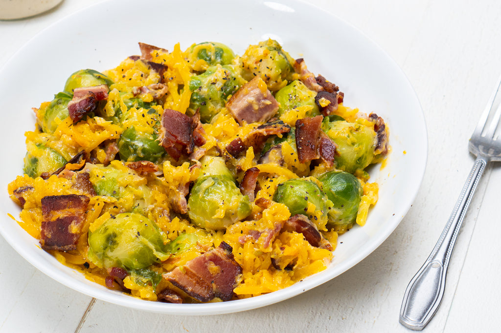 Butternut squash noodles with Brussels sprouts, bacon, and Primal Kitchen No Dairy Alfredo Sauce on a white plate with a silver fork