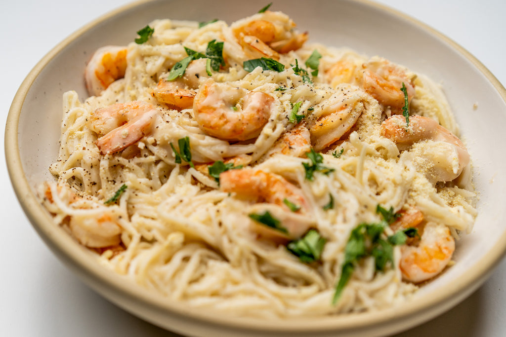 Shrimp alfredo with no dairy garlic sauce is prepared in a cream colored bowl, topped with parsley.