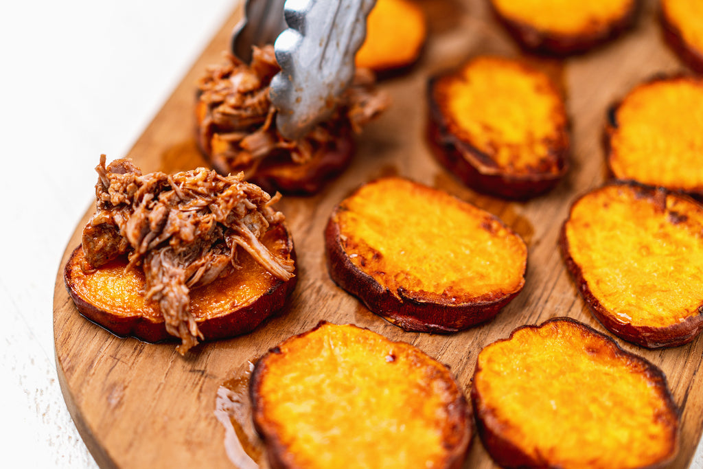 Metal tongs place pulled pork on baked sweet potato rounds.