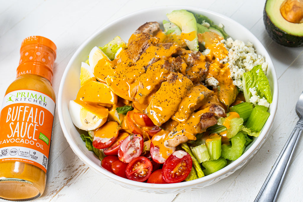 Chicken cobb salad with Buffalo Ranch dressing in a large white bowl. Next to the bowl is Primal Kitchen Buffalo Sauce, a silver fork, and half of an avocado.