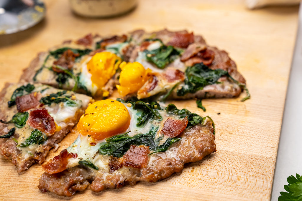 A breakfast meatza pie is sliced into four slices, with ingredients nearby on a cutting board.