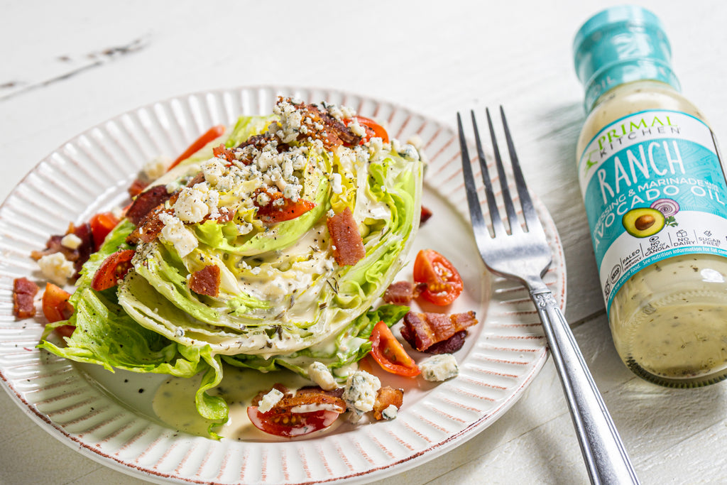 Iceberg wedge salad topped with sliced cherry tomatoes, crumbled bacon, blue cheese crumbles, and ranch dressing on a white plate with a silver fork. A bottle of Primal Kitchen Ranch Dressing is next to the plate.