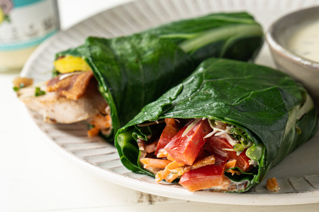 Two collard wrap halves filled with chicken, bacon, sprouts, carrots, bell peppers, and ranch dressing on a white plate. A ramekin of more ranch dressing is on the plate.