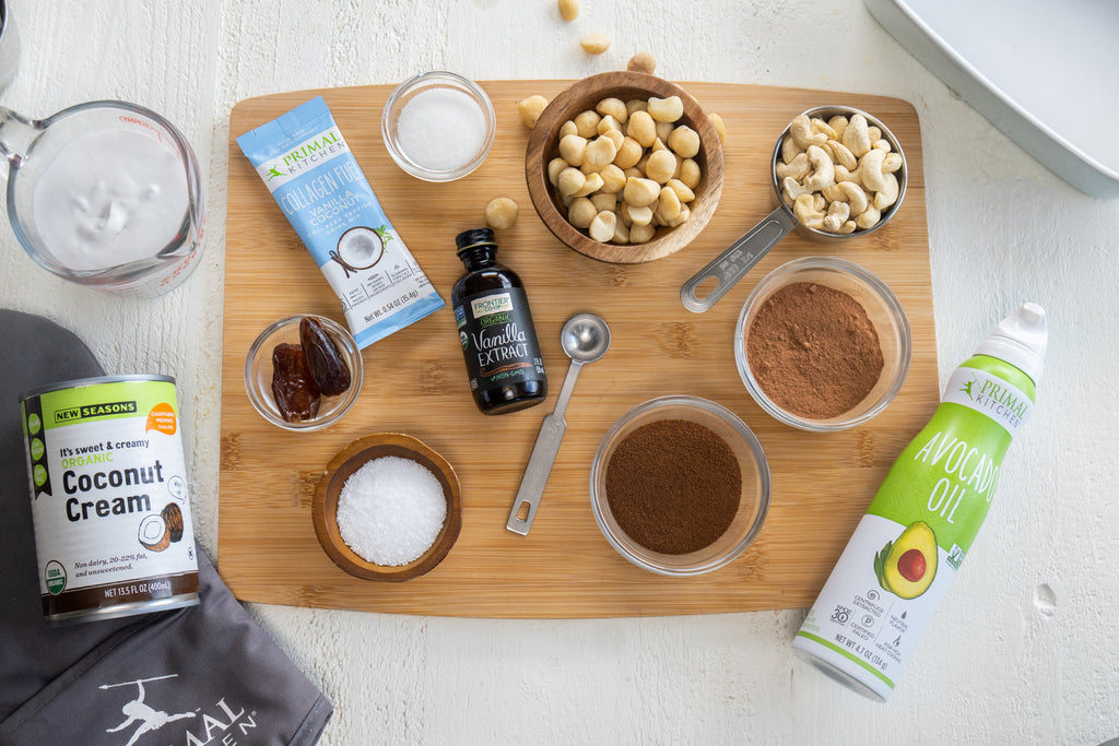 Baked noatmeal ingredients spread out on a wood cutting board. Ingredients include: Primal Kitchen Avocado Oil Spray, pure vanilla extract, coconut milk, Primal Kitchen Collagen Fuel - Vanilla, macadamia nuts, cashews, espresso powder, salt, granulated monk fruit, and cocoa powder.