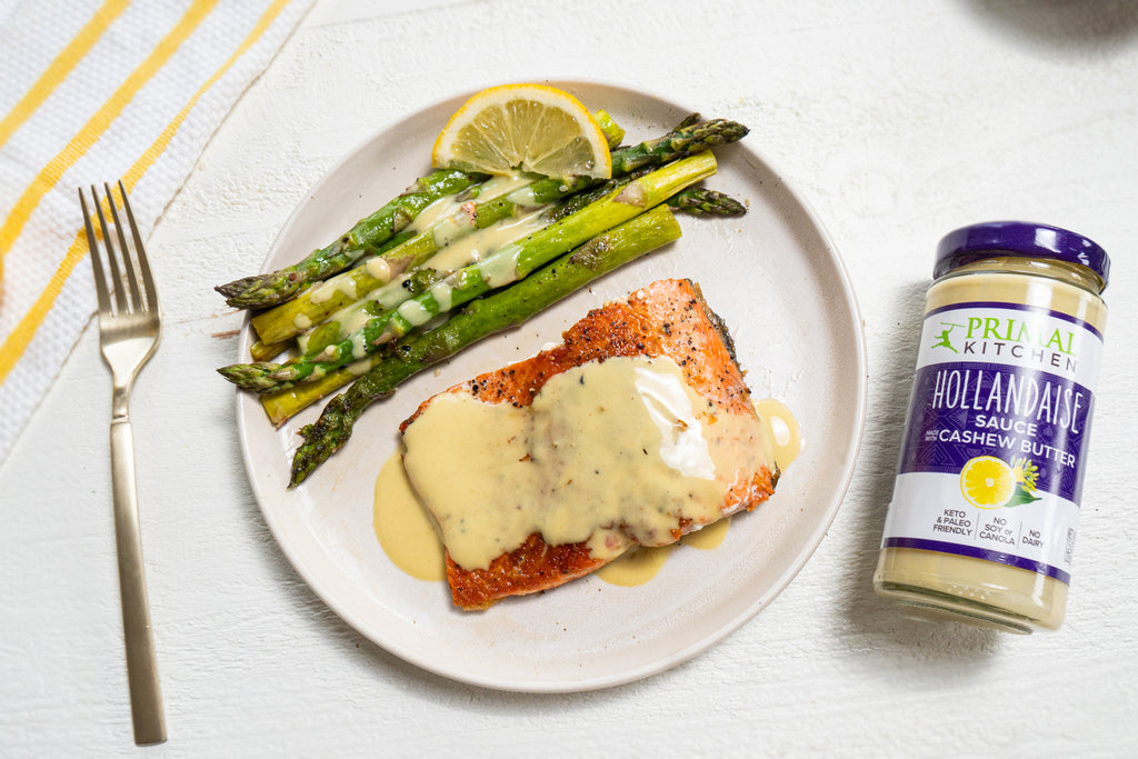 Salmon and asparagus with hollandaise sauce are on a white plate with a jar of hollandaise, a fork, and a yellow tea towel.