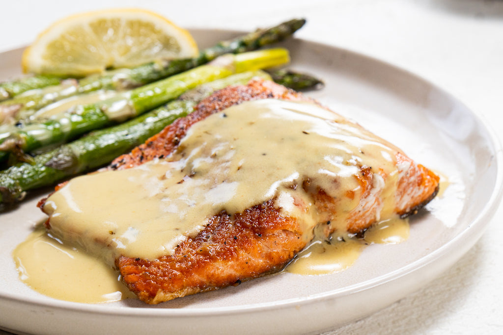 A closeup of salmon covered in hollandaise sauce with lemon and asparagus also on the plate.