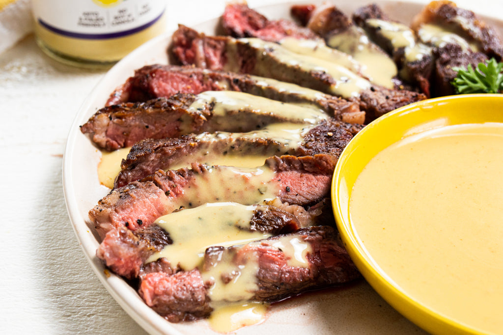 Steak is drizzled with hollandaise with a yellow saucer of hollandaise.
