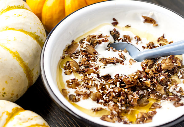 Pumpkin spice granola on top of yogurt in a white bowl with a spoon
