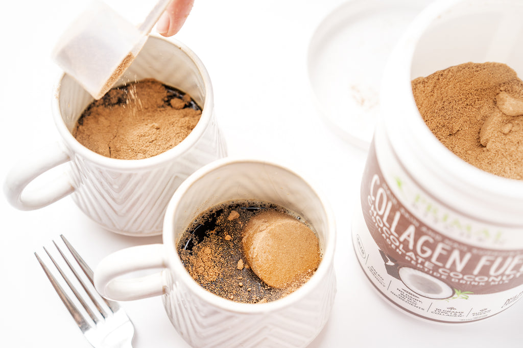 Adding Primal Kitchen Chocolate Collagen Fuel to mugs of hot coffee