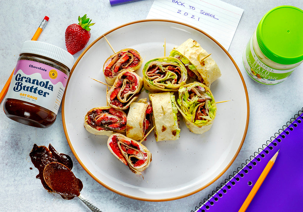 A white plate with sweet and savory pinwheels is surrounded by ingredients and school supplies.