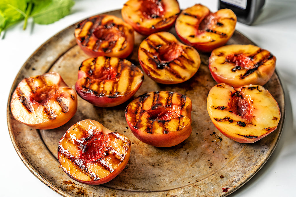 Grilled peach halves on a wooden plate