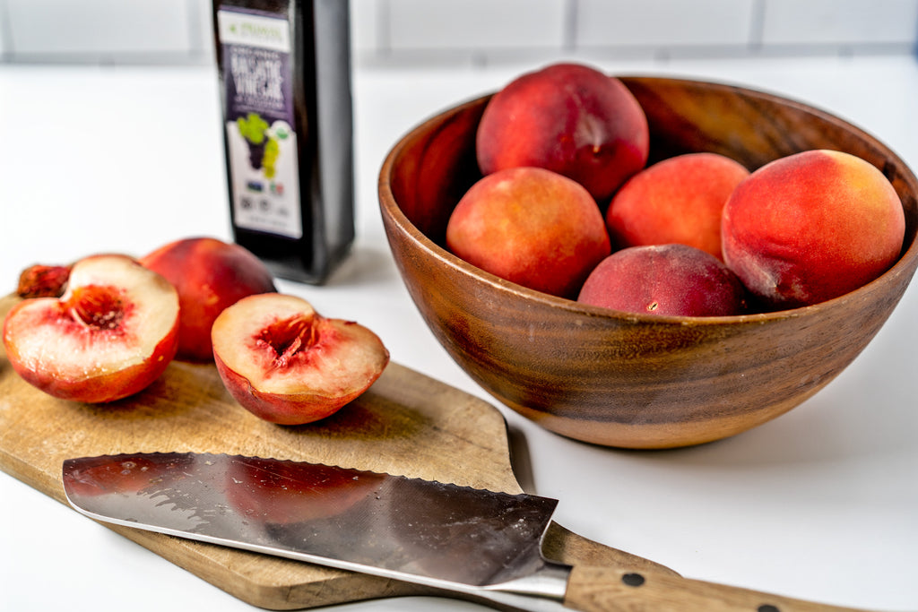Peaches cut in half on a cutting board next to a bowl of peaches and Primal Kitchen Balsamic Vinegar of Modena
