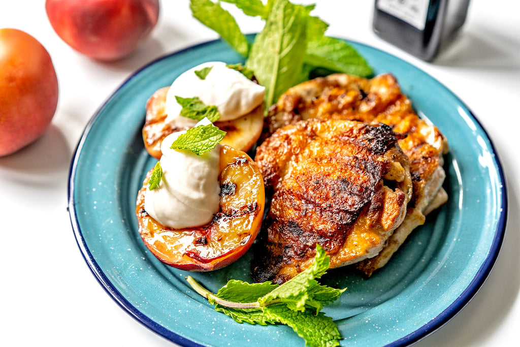 Blue plate with grilled chicken thighs and grilled peaches with whipped cream and mint