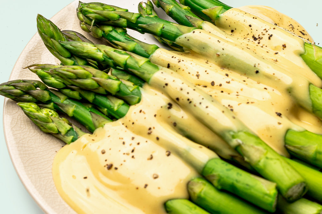 Close up shot of a white plate of steamed asparagus topped with Primal Kitchen Hollandaise Sauce. On top of the asparagus with hollandaise sauce is cracked black pepper.