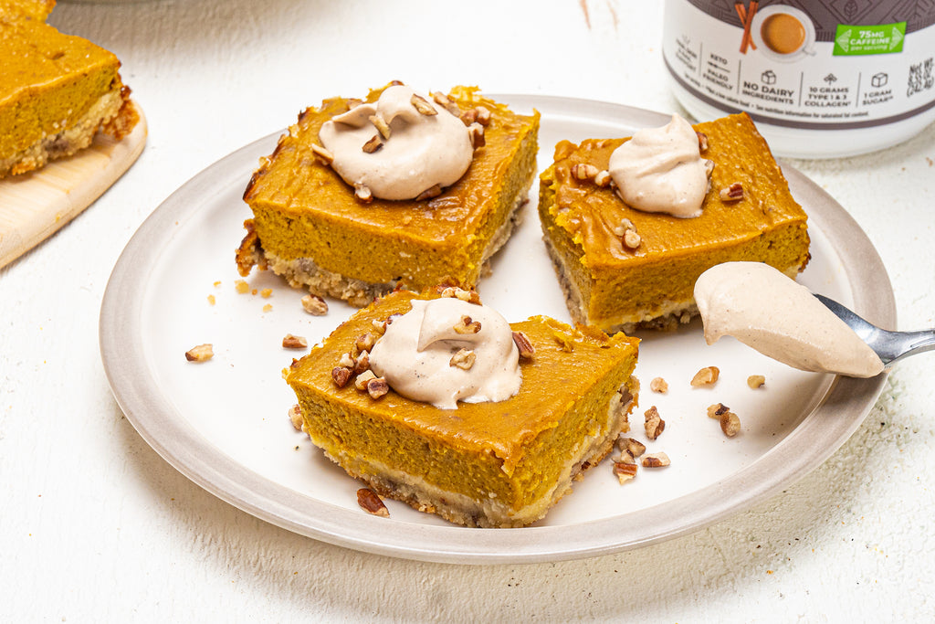 Pumpkin pie bars with coconut whipped cream on a white plate with chopped pecans on top