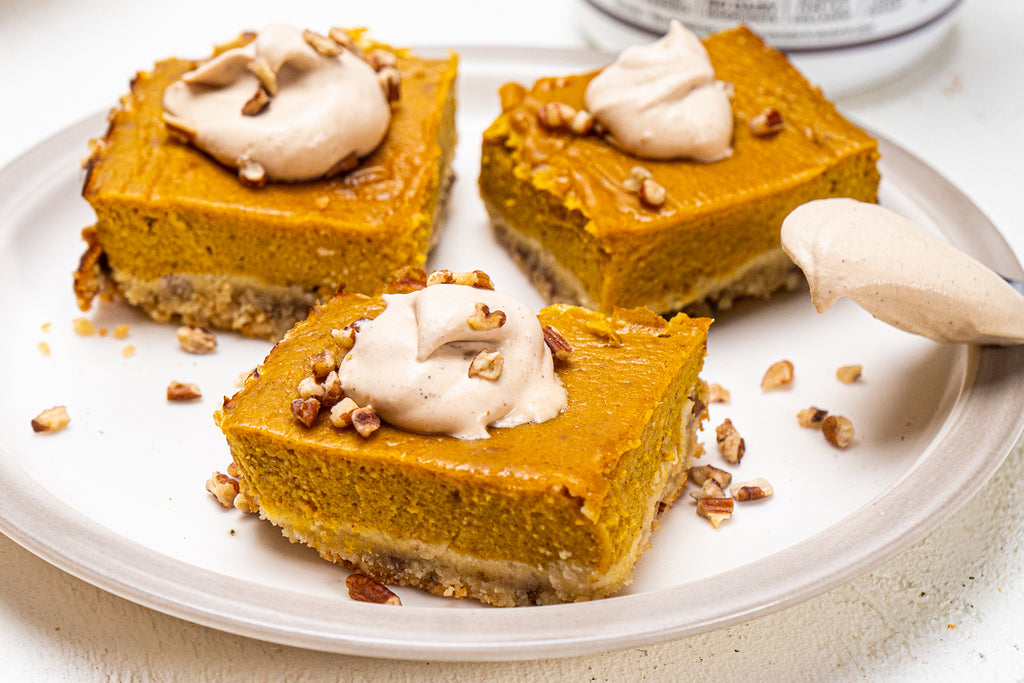 Close up shot of pumpkin pie bars with coconut whipped cream on a white plate