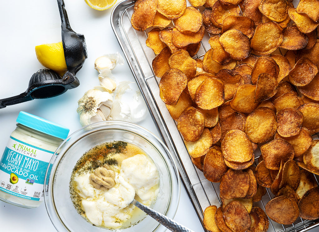 Homemade potato chips on a baking sheet next to a handheld juicer with half a lemon. A bowl of vegan blue cheese dressing with a spoon in it and Primal Kitchen Vegan Mayo and garlic cloves are off to the side.