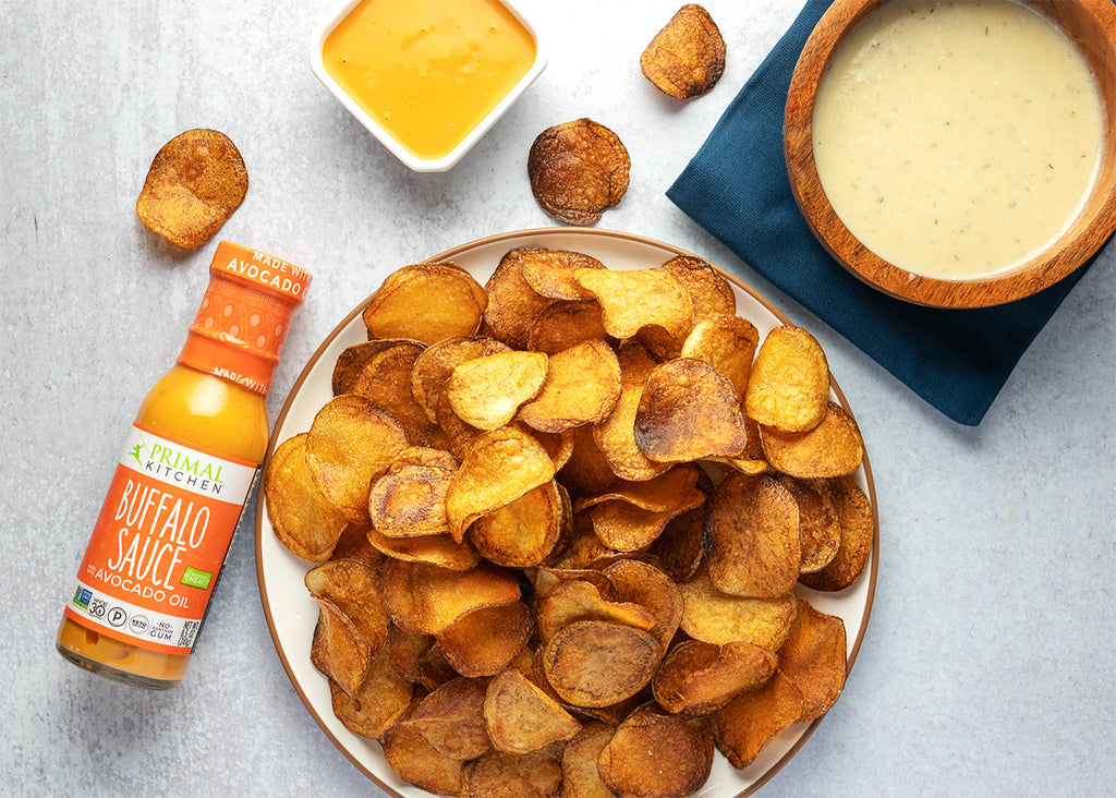 Homemade potato chips on a white plate next to Primal Kitchen Buffalo Sauce and vegan blue cheese dressing in a bowl.