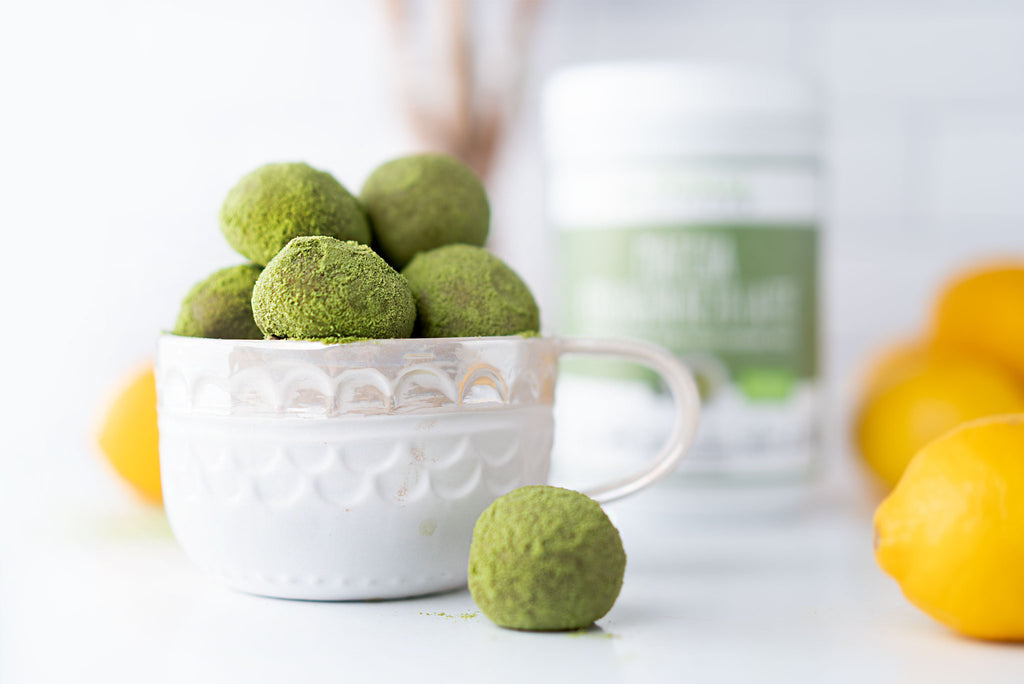 Matcha balls stacked in a white bowl. A canister of Primal Kitchen Matcha Collagen Keto Latte Drink Mix is blurred in the background.