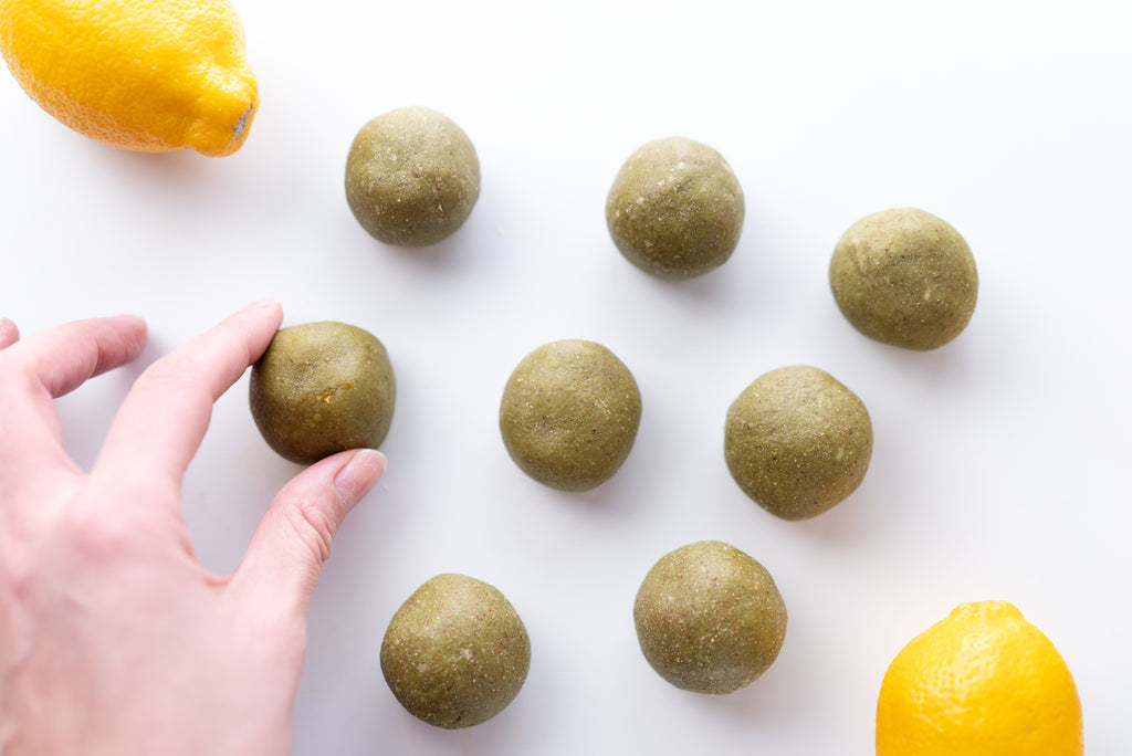 A hand placing a rolled matcha ball onto a white counter top. Other matcha balls and lemons are also in the photo.