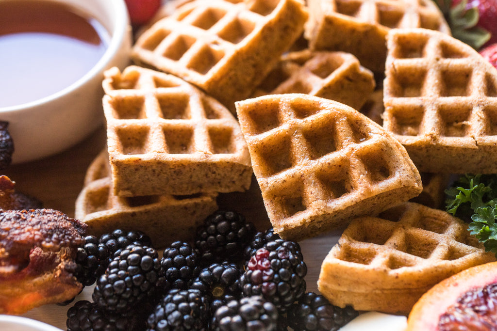 Vanilla collagen waffles are cut into triangle slices and arranged next to berries.