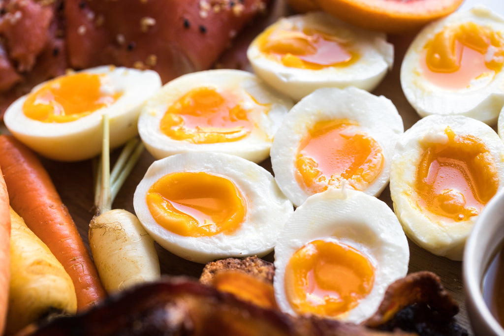 A closeup of the charcuterie board shows the jammy eggs with yellow yolks.