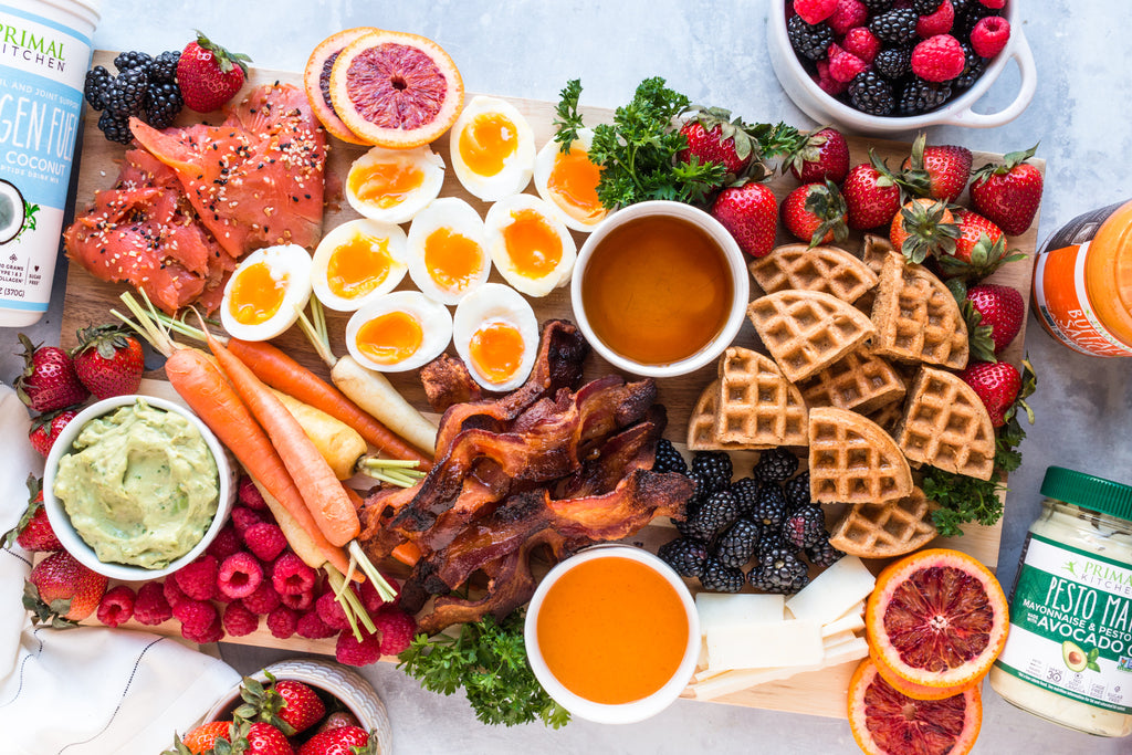 An overhead closeup shows a breakfast grazing board overflowing with breakfast foods like waffles, eggs, bacon, and crudite.