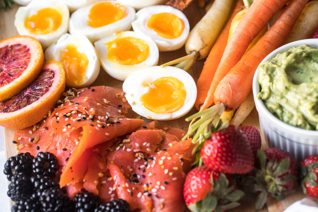 A closeup of the breakfast charcuterie board shows eggs, crudite, salmon, and creamy guacamole made with mayo.