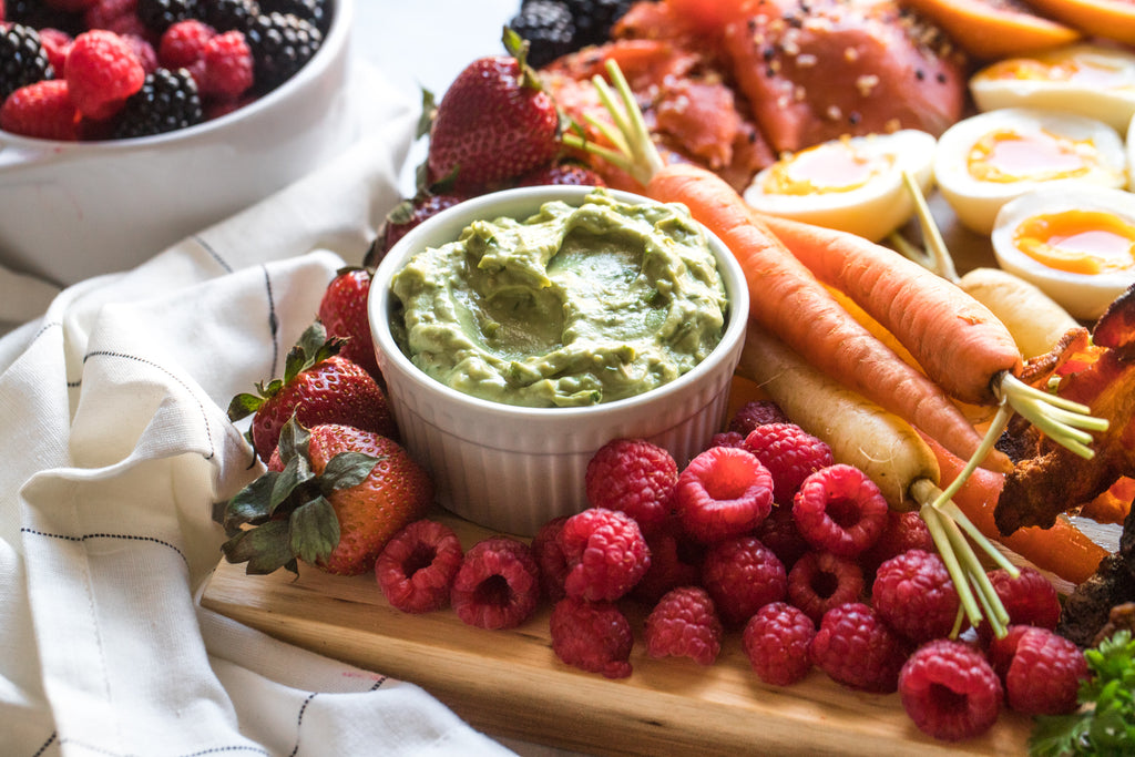 A small bowl of creamy guacamole made with mayo is surrounded by fresh veggies and fruit on the board.