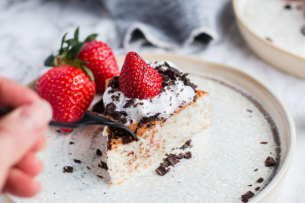 a slice of keto angel food cake topped with whipped cream, chocolate shavings, and a strawberry