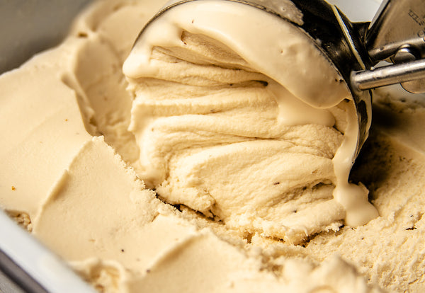 Close up image of ice cream scoop scooping salted caramel ice cream