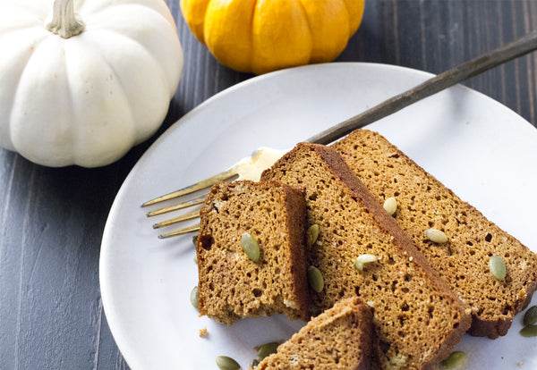 Pumpkin bread slices on a white plate with a fork