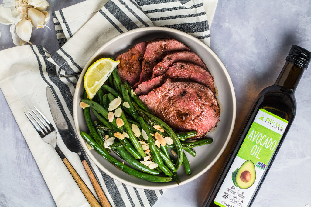 Sauteed green beans with sliced almonds and a lemon wedge on a white plate. Sliced, cooked steak on the plate. A fork and knife, blue and white napkin, and Primal Kitchen Avocado Oil is next to the plate.