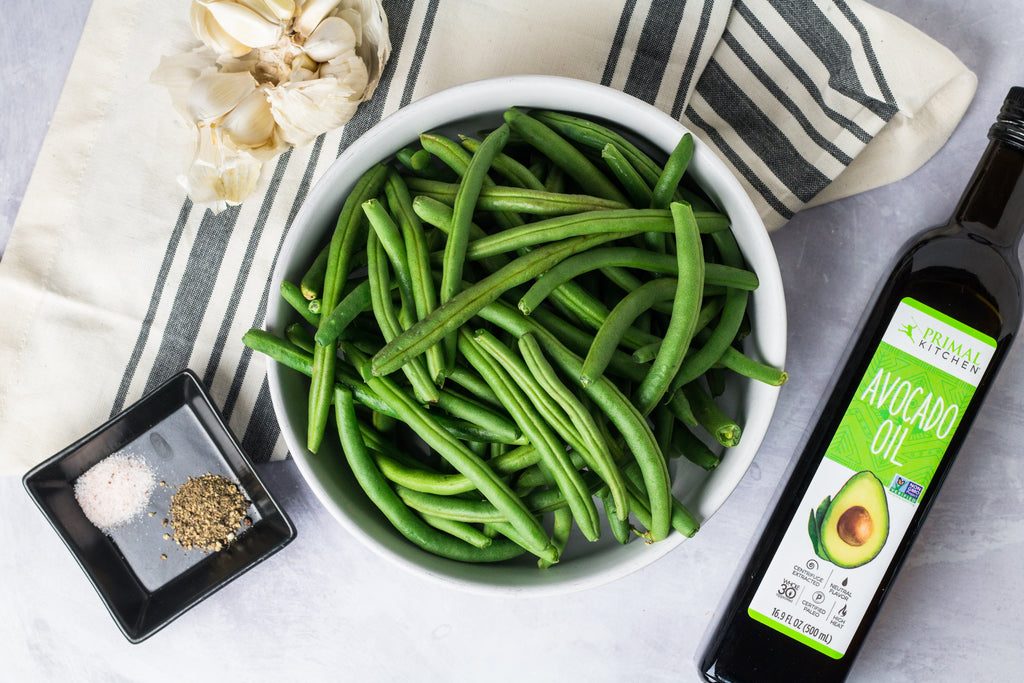 A large white bowl filled with raw green beans with a bottle of Primal Kitchen Avocado Oil, garlic cloves, and a black dish with salt and pepper next to the bowl. Bowl resting on top of a blue and white napkin.