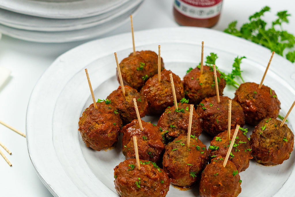 Slow cooker BBQ meatballs with toothpicks stuck in the tops, garnished with chopped parsley, on a white plate. White plates stacked in the background with fresh parsley and Primal Kitchen Classic BBQ Sauce