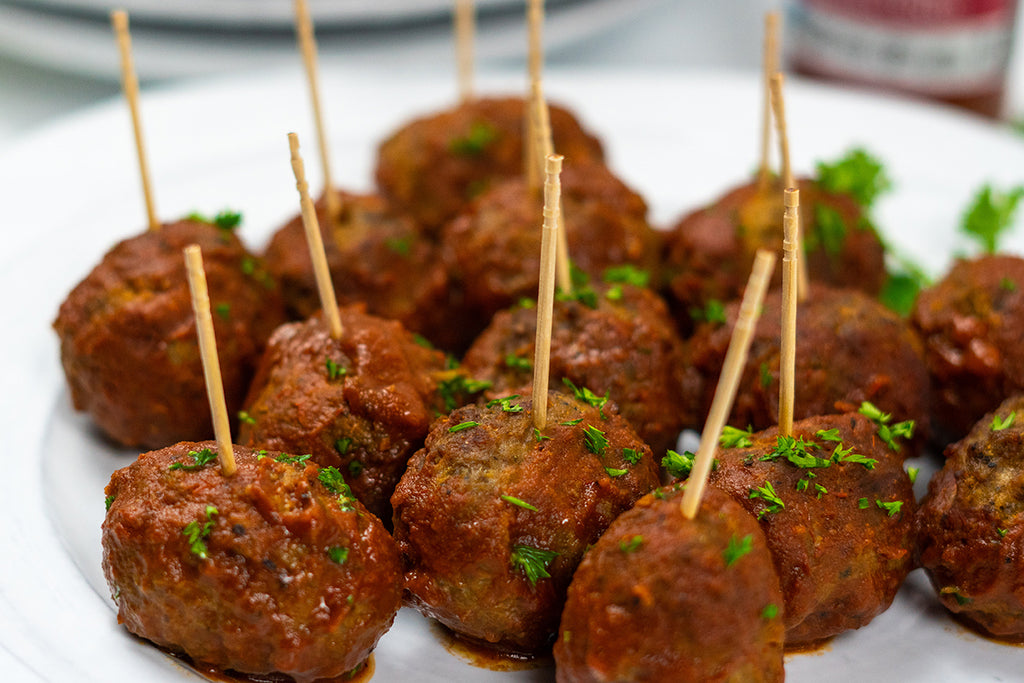 Slow cooker BBQ Meatballs on a white plate garnished with parsley with toothpicks stuck in the tops