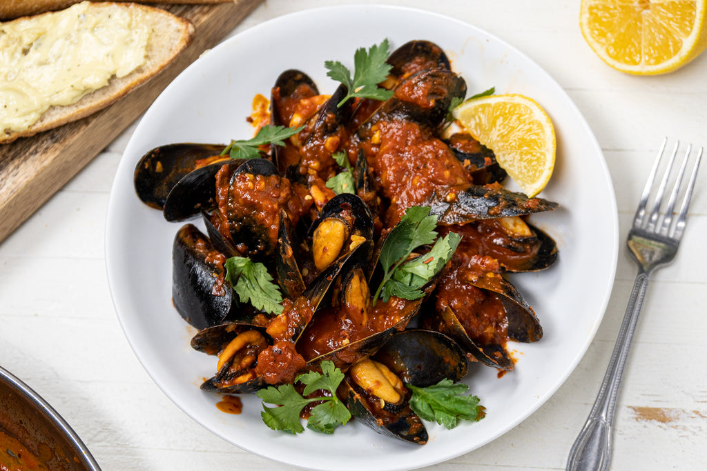 A white dish of Mussels Fra Diavolo with a fork, lemon wedge and buttered bread nearby.