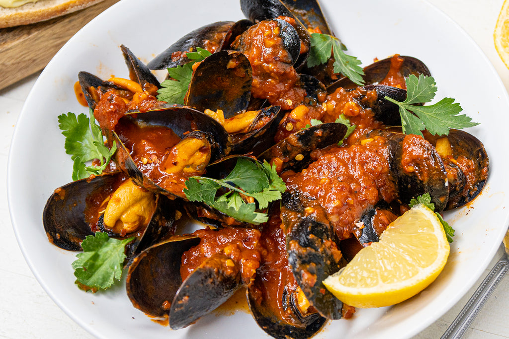 Spicy mussels in arrabbiata sauce in a white dish with fresh parsley and lemon.