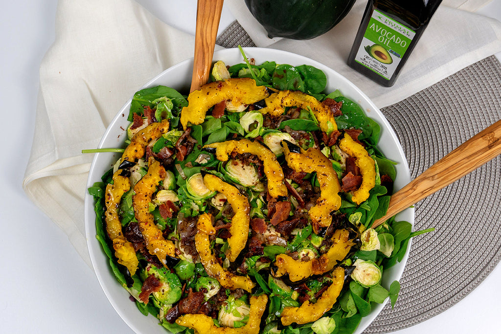 Fall salad in a white bowl with wooden tongs overhead shot