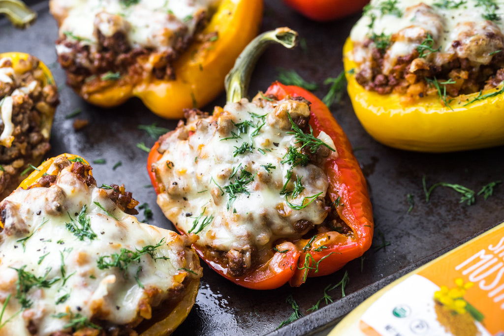 A closeup shows stuffed bell peppers on a black pan with mustard in the foreground.