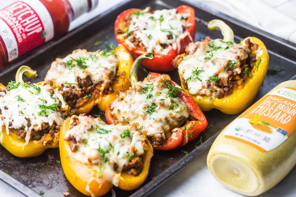 6 stuffed peppers are arranged on a baking pan with ketchup and mustard nearby.