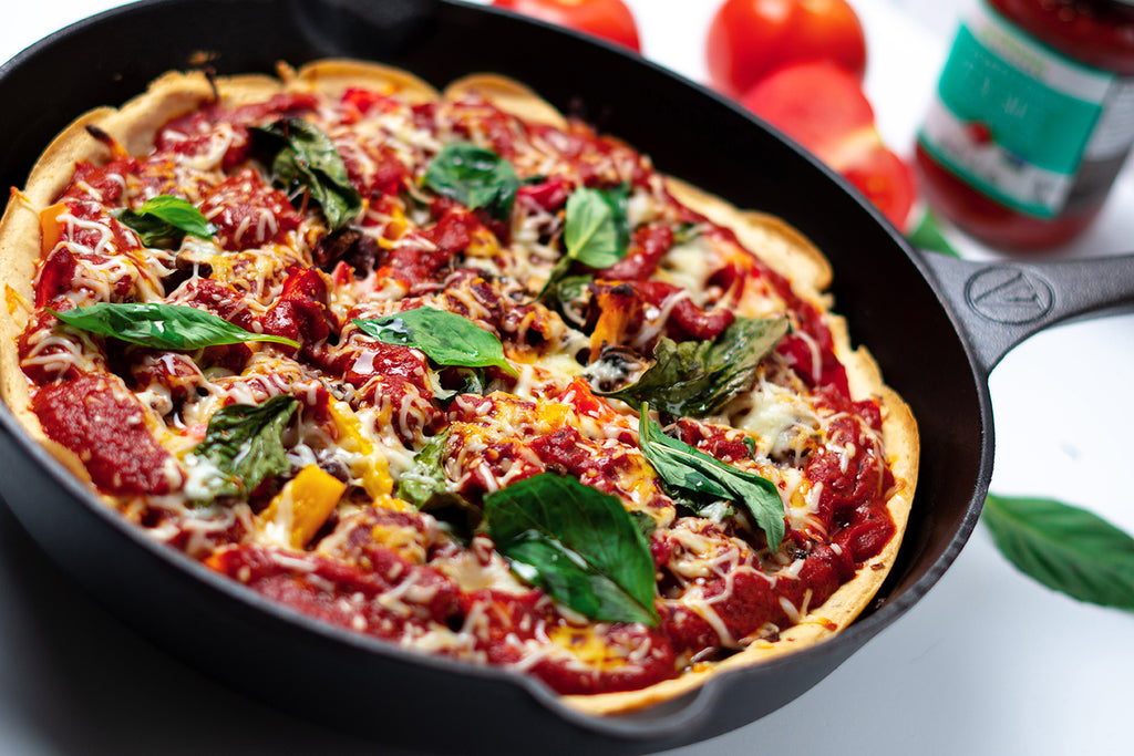 Deep dish pizza topped with basil in a cast iron skillet