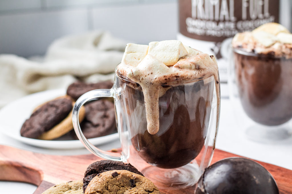 Hot chocolate bomb melted in a clear mug on a cutting board next to solid hot chocolate bombs. Hot chocolate is topped with cubed marshmallows.