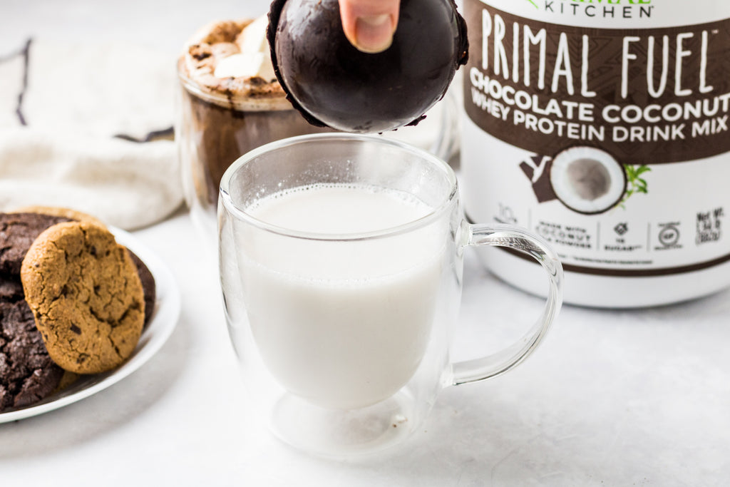 Hand holding hot chocolate bomb over a clear mug with hot milk. A plate of cookies and Primal Kitchen Primal Fuel in the background.