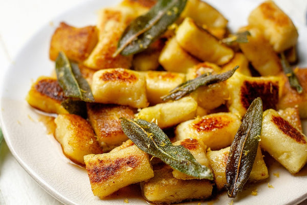 Cauliflower gnocchi with fried sage on a white plate