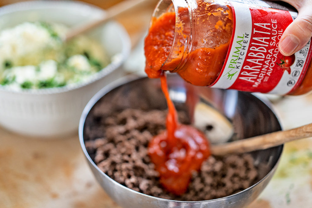 Hand pouring Primal Kitchen Arrabbiata Sauce into a bowl with cooked ground beef