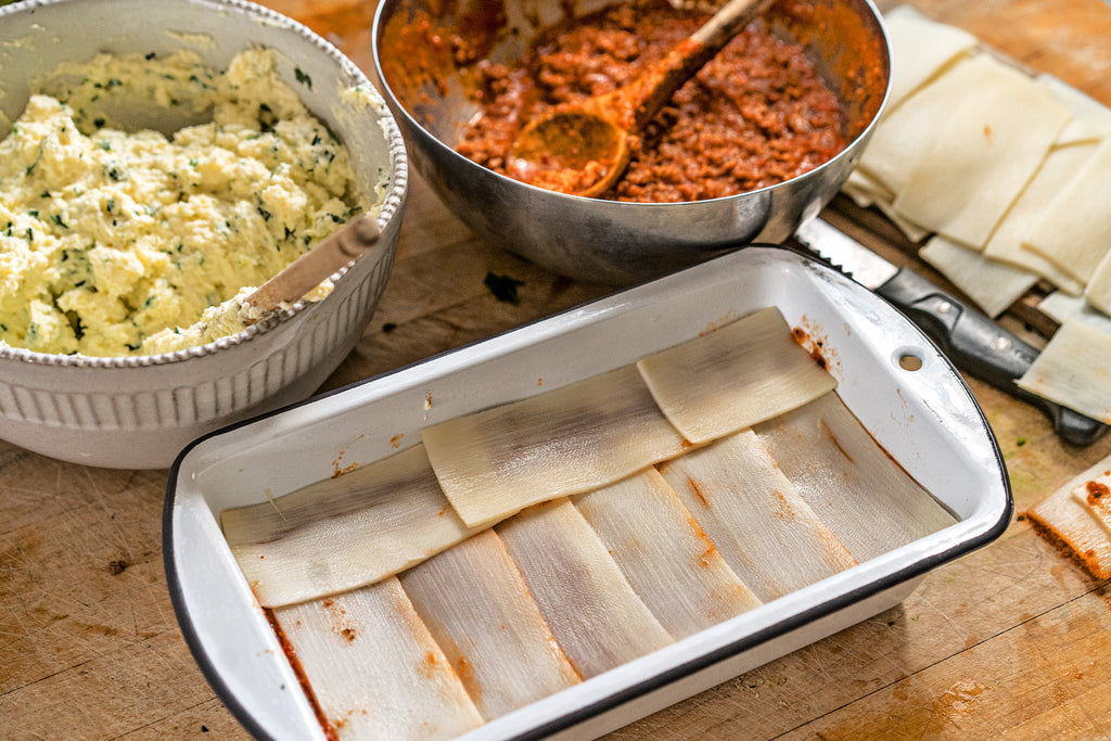Palmini lasagna noodles layered in a baking dish next to a bowl of spicy meat sauce and a bowl of cheese mixture