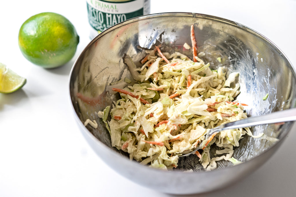 Coleslaw in a metal mixing bowl with Primal Kitchen Pesto Mayo and fresh lime in the background